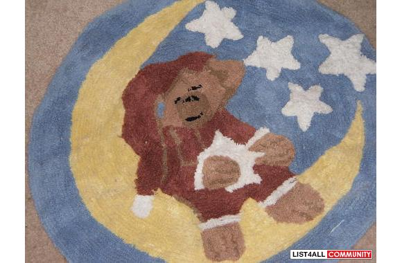 A kids area rug.Really cute.Bear hanging of a moon with stars around i
